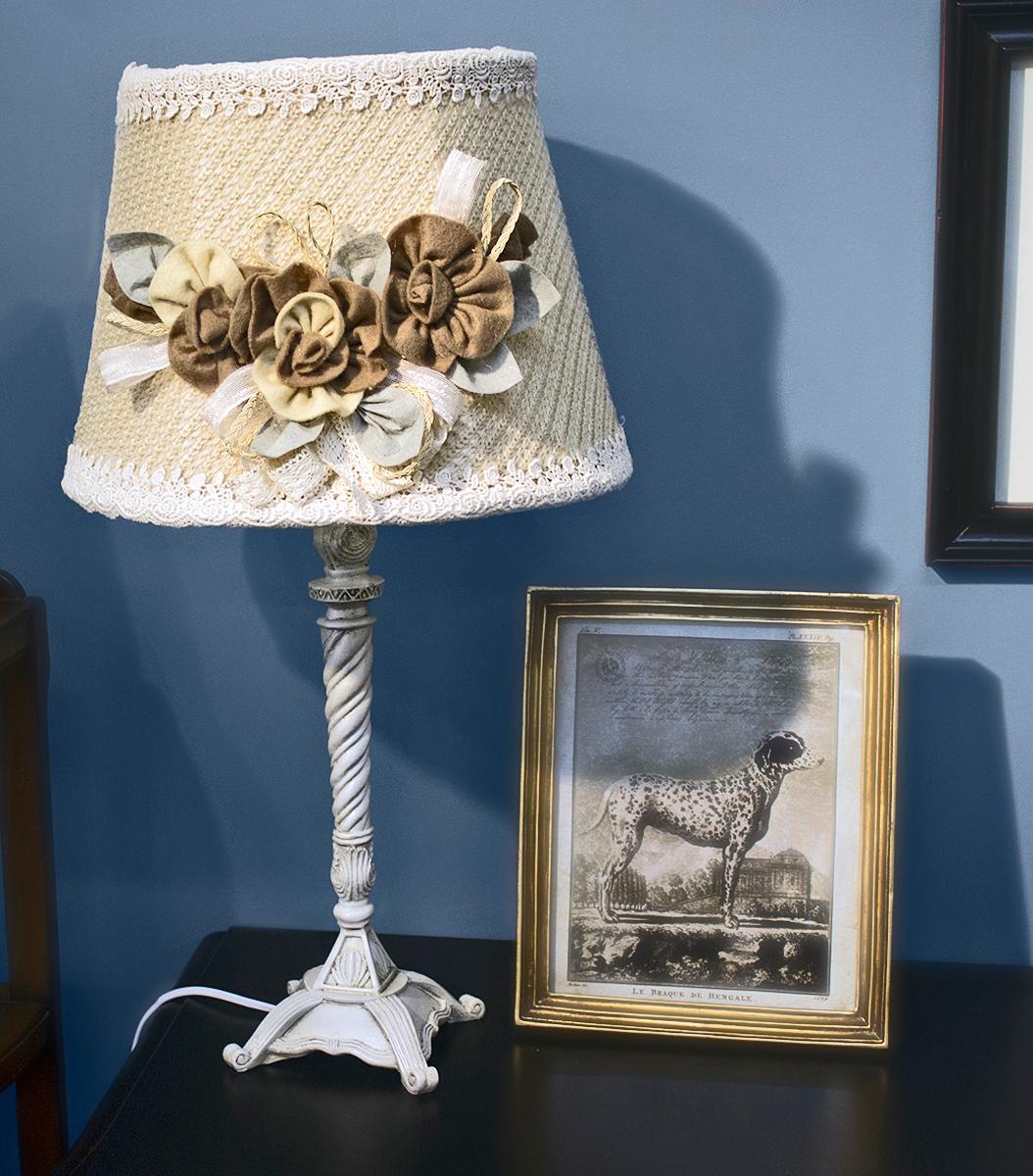 """Лампа настольная ручной работы """"Estro"""" станет украшением вашей комнаты и оригинально дополнит интерьер. Такой светильник отлично подойдет для освещения кабинета, спальни или гостиной. Лампа выполнена из бежевого металла. Абажур лампы изготовлен из полиэстера и дополнен текстильным украшением.К светильнику предусмотрен цоколь Е14 для лампы мощностью 40 Вт.Высота лампы: 60 см."""