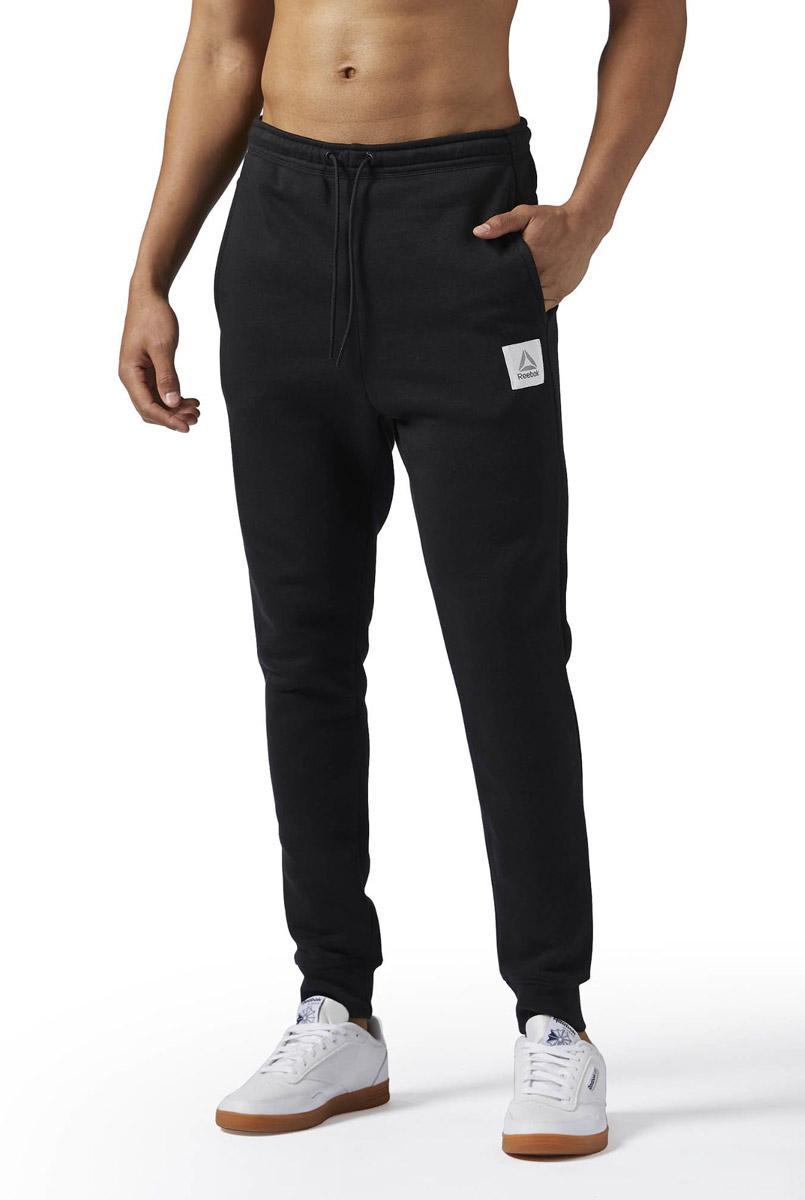 Брюки спортивные мужские Reebok Cs Jogger Pant, цвет: черный. BQ2533. Размер XXL (60/62)BQ2533Спортивные мужские брюки Reebok выполнены из натурального хлопка с добавлением полиэстера. Модель дополнена по боком прорезными карманами. Эластичный пояс на шнурке и манжеты на лодыжках, обеспечат оптимальную посадку. Модель дополнена логотипом бренда.