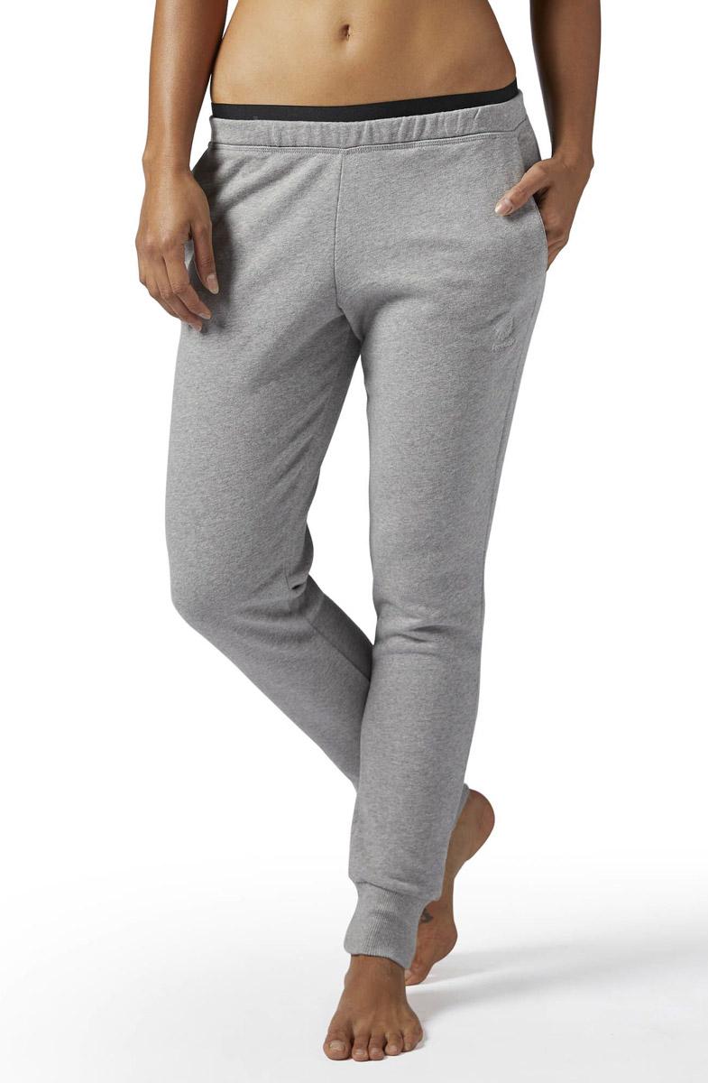 Брюки спортивные женские Reebok F Ft Pant, цвет: серый. BS3813. Размер L (50/52)BS3813Спортивные женские брюки Reebok выполнены из натурального хлопка. Зауженный крой этой модели создает изящный силуэт. Благодаря удобным карманам брюки отлично подойдут на каждый день. Эластичный пояс и манжеты на лодыжках обеспечат оптимальную посадку. Модель дополнена трехцветными нашивками и логотипом бренда.