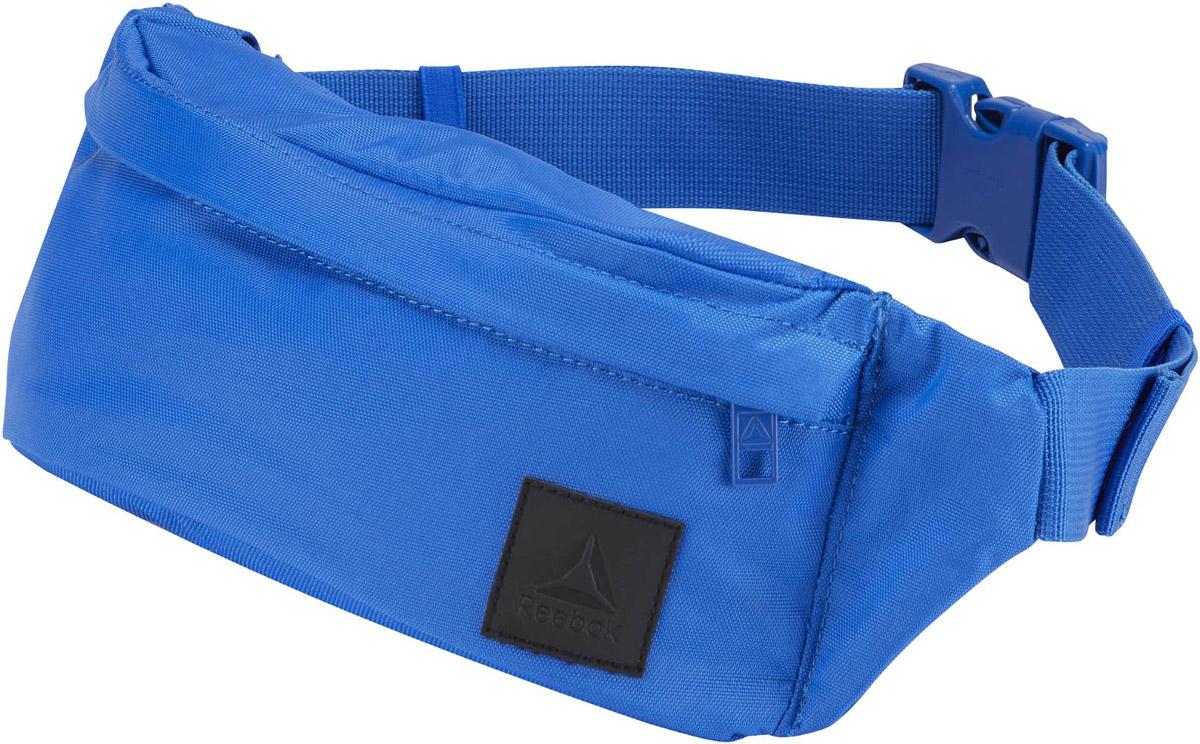 Сумка на пояс Reebok Style Found Waistba, цвет: синий. CD2181CD2181Наденьте сумку Reebok Style Found Waistba на пояс и отправляйтесь навстречу приключениям. Внутри основного отделения на молнии есть несколько отсеков, куда можно положить телефон, бумажник и ключи. Регулируемый ремень позволяет носить сумку на поясе или на плече. Так, как удобно вам!Материал: 100% нейлон, легкий и в то же время прочный тканый материал.Размеры: 10.5 х 32 х 6 см.Удобный регулируемый ремень.Карман на молнии спереди.Потайной карман сзади.