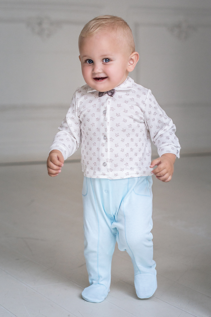 Комбинезон домашний для мальчика Мамуляндия Маленький принц, цвет: молочный, голубой. 17-302. Размер 5617-302Комбинезон для мальчика Мамуляндия Маленький принц изготовлен из натурального хлопка. Модель с отложным воротником, длинными рукавами и закрытыми ножками имеет удобную центральную застежку на кнопки. Изделие оформлено набивным рисунком, декорировано атласным бантиком.