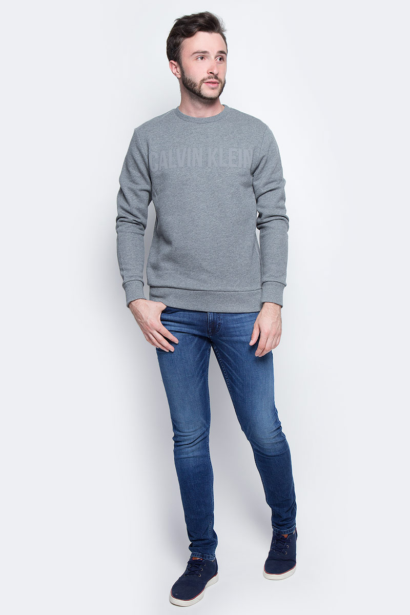Джемпер мужской Calvin Klein Jeans, цвет: серый. J30J305608_0250. Размер XXL (52/54)J30J305608_0250Джемпер Calvin Klein выполнен из 100% хлопка. Модель имеет круглый вырез горловины и длинные стандартные рукава. Манжеты рукавов, низ джемпера и горловина отделаны эластичной резинкой. Модель на груди дополнена надписью с названием бренда.