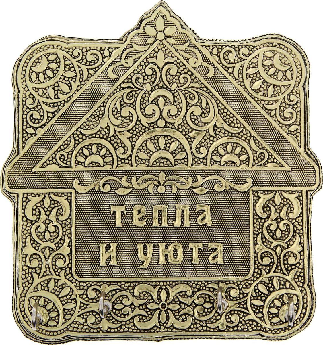 Ключница настенная Тепла и уюта, цвет: золотистый, 15,3 х 16,1 х 3,2 см1259440Как важно, чтобы в доме всё находилось на своих местах, особенно те вещи, которые имеют привычку пропадать в самый неподходящий момент. Например, ключи! Порядок в доме обеспечит прочное изделие, выполненное из крепкого алюминия и дерева лучшими мастерами Индии. Узорчатая ключница в форме дома принесёт уют и счастье в ваш дом. Крепление на обороте позволяет легко прикрепить её к стене. Такая ключница станет и прекрасным подарком близким, и незаменимым украшением дома!