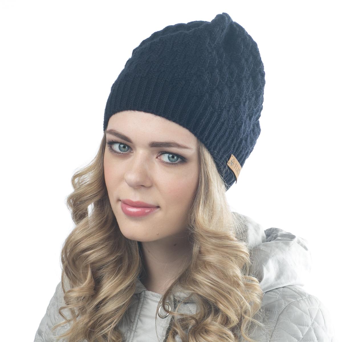 Шапка женская Flioraj, цвет: темно-синий. 01FJ. Размер 56/5801FJТеплая шапка от Flioraj, связанная из овечьей шерсти и шерсти горной альпаки, отлично согреет в холодную погоду. Состав пряжи делает изделие мягким, теплым и комфортным. Модель выполнена крупной рельефной вязкой и украшена нашивкой из натуральной кожи.