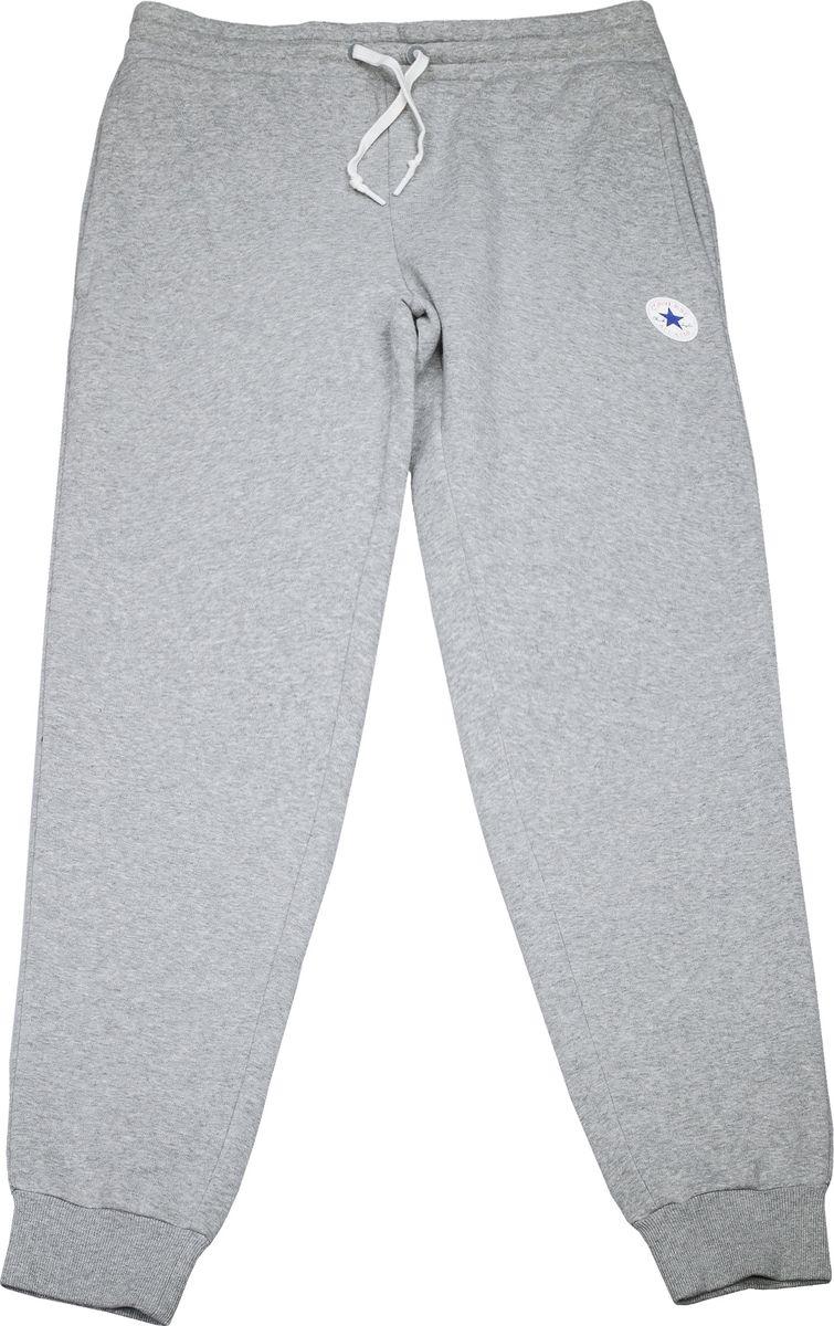 Брюки спортивные мужские Converse Core Jogger, цвет: серый. 10004631035. Размер M (48)10004631035Мужские спортивные брюки изготовлены из качественного трикотажа на основе хлопка. Модель на широкой эластичной резинке и шнурке на талии дополнена боковыми карманами. Брючины снизу оформлены широкими резинками. Такие брюки незаменимая вещь в спортивном и летнем гардеробе. Прекрасный выбор для занятий спортом или активного отдыха.