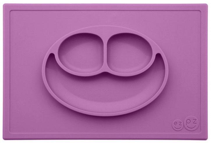 Ezpz Тарелка детская Happy Mat цвет черничныйPKHMB004Необычная силиконовая тарелка-плейсмат, которая не имеет аналогов. Ее главная особенность заключается в том, что тарелку невозможно перевернуть. С ней ребенок не сможет испачкать стол или, что гораздо важнее, обжечься горячей пищей. Изготовлена из силикона высочайшего качества, не имеет липучек или присосок - фиксация происходит на любой ровной горизонтальной поверхности за счет плоской поверхности мата. Подходит для использования в микроволновке и посудомоечной машине. Выглядит, как улыбающаяся рожица, что очень нравится детям и их мамам. Объем: 540 мл