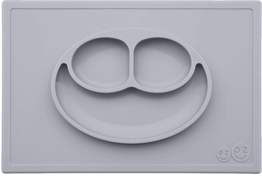 Ezpz Тарелка детская Happy Mat цвет светло-серыйPKHMP003Необычная силиконовая тарелка-плейсмат, которая не имеет аналогов. Ее главная особенность заключается в том, что тарелку невозможно перевернуть. С ней ребенок не сможет испачкать стол или, что гораздо важнее, обжечься горячей пищей. Изготовлена из силикона высочайшего качества, не имеет липучек или присосок - фиксация происходит на любой ровной горизонтальной поверхности за счет плоской поверхности мата. Подходит для использования в микроволновке и посудомоечной машине. Выглядит, как улыбающаяся рожица, что очень нравится детям и их мамам. Объем: 540 мл