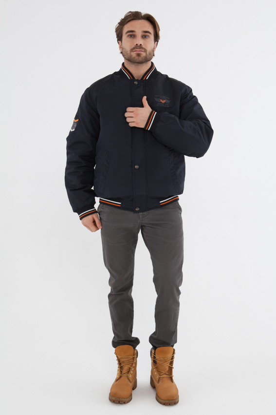 Куртка мужская Vizani, цвет: синий. 10588С_99. Размер 5210588С_99Стильная мужская куртка-бомбер Vizani выполнена из нейлона с синтепоновым утеплителем. Модель застегивается на молнию и ветрозащитную планку с кнопками. Горловина, манжеты рукавов и низ изделия отделаны трикотажной резинкой. Куртка дополнена двумя боковыми внешними карманами и тремя внутренними карманами на молниях.