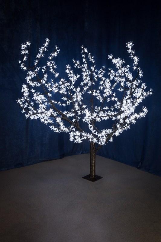 Светодиодное дерево Neon-Night Сакура, цвет: белый, диаметр кроны 180 см, высота 150 см531-105Световое дерево Сакура представляет собой имитацию цветущей японской сакуры. Оно используется для декоративного освещения интерьеров и ландшафтов. Такое дерево может стать прекрасным украшением для вашего дома, офиса, торгового зала, кафе, ресторана или загородного участка. Оно создаст уют, придаст оригинальный стиль и необходимый вам колорит независимо от времени года. Конструкция имеет лекгосплавной каркас в оболочке из темного пластика. На ветках дерева расположены яркие светодиодные гирлянды с силиконовыми насадками (цветками). Светодиодное дерево выглядит очень натурально.Питание осуществляется через сетевой трансформатор, поэтому изделие является низковольтным и может использоваться в уличных условиях. Диаметр кроны: 1,8 м. Высота дерева: 1,5 м. 864 лепестка.
