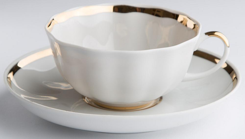Чашка чайная Дулевский Фарфор Тюльпан. Московский с лентой, с блюдцем, 220 мл036962Фарфоровая посуда считается классикой, ведь никакое время для нее не властно. Впервые появившись в Китае, фарфор присутствовал в домах богатых людей и являлся драгоценным подарком для любого европейца. Фарфор ценили на вес золота, и это неудивительно, ведь его качество и необыкновенные свойства славились на весь мир. Так, например, чайники из фарфора - это настоящая находка для ценителей чайной ароматной церемонии. Благодаря своим свойствам, фарфор способен удерживать тепло напитка продолжительное время. Чашка Тюльпан. Московский с лентой имеет довольно простой рисунок на белоснежном фарфоре, который несомненно, привлечет Ваше внимание. Фарфор производства Дулевский Фарфор имеет высокую термическую и механическую стойкость, благородный внешний вид. Чашка чайная Дулевский ФарфорТюльпан. Московский с лентой станет прекрасным украшением сервировочного стола. Чай из такого изделия будет невероятно ароматным и вкусным.