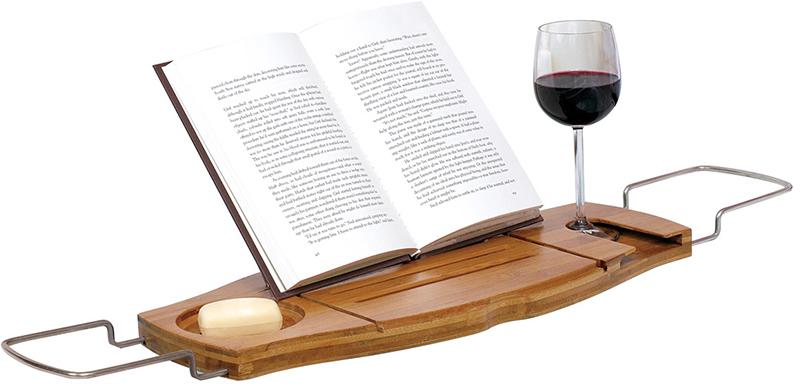 """Полка для ванной Umbra """"Aquala"""" изготовлена из экологически чистого натурального бамбука. Позвольте себе провести уютный вечер в ванне. Только вы, пена, бокал вина, книга и полная релаксация. На полке достаточно места для вазочки с фруктами или ароматной свечи, так что вы буквально почувствуете себя в спа-салоне. Раздвигается под любую ширину ванны (до 102 см). Упакована в фирменную коробку."""