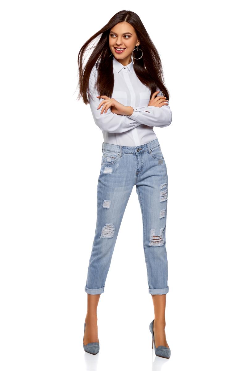 Джинсы женские oodji Ultra, цвет: голубой джинс. 12105101-2/42559/7000W. Размер 27 (44)12105101-2/42559/7000WДжинсы от oodji с прорехами выполнены из хлопкового денима. Модель Boyfriend в поясе застегивается на пуговицу, имеет ширинку на молнии и шлевки для ремня. Джинсы имеют классический пятикарманный крой.