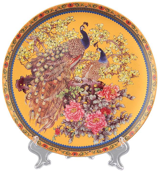 Тарелка декоративная Elan Gallery Павлин золотой, с подставкой, цвет: желтый, диаметр 18 см180764Декоративная тарелка Elan Gallery Павлин золотой, изготовленная из фарфора, станет необыкновенным подарком и прекрасным украшением вашего интерьера.Тарелка оснащена петелькой для подвешивания, а также ее можно разместить на пластиковой подставке, которая входит в комплект.