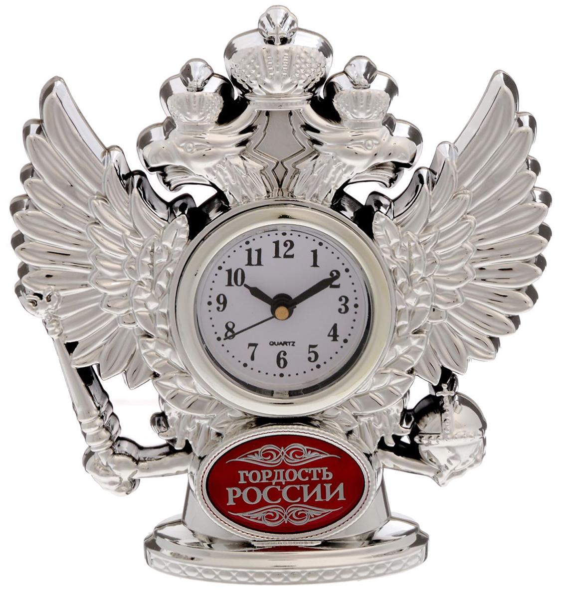 Часы настольные Гордость России, 11 х 12 см. 16929181692918Изделие созданоы для истинных патриотов с твёрдым характером. Двуглавый орёл, словно стоит на страже вашего времени, обрамляя циферблат и придавая предмету статусный облик. Изделие прекрасно дополнит письменный стол или стеллаж в кабинете, ведь это не просто часы, но и стильная статуэтка. На обратной стороне вы найдёте мотивирующую на покорение всего мира надпись! Инструкция Аккуратно достаньте механизм с циферблатом из корпуса. Установите время с помощью колёсика. Вставьте механизм обратно. Часы работают от батареек AG 13. Сувенир преподносится в подарочной коробочке с прозрачным окном.