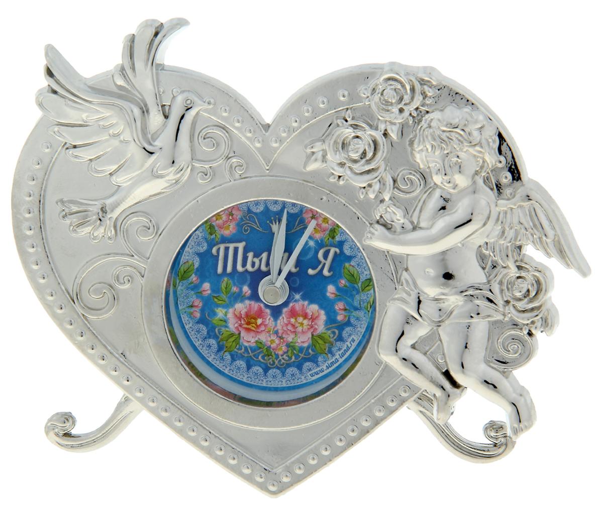 """Часы """"Ты и Я"""" - это олицетворение неповторимой грации в декоративном элементе интерьера. Они придутся по душе натурам романтичным и нежным, предпочитающим необычные детали в оформлении дома. Символы любви – голубь и Купидон – придают изделию неповторимый шарм. Часы выполнены из металла c ярким циферблатом, располагаясь на прочных ножках, и работают от батареек LR44 (не входят в комплект). Кроме того, они включают функцию будильника, что делает их не только красивыми, но и полезными. Теперь вы ни за что не проспите важное событие и будете встречать каждый новый день с улыбкой!"""