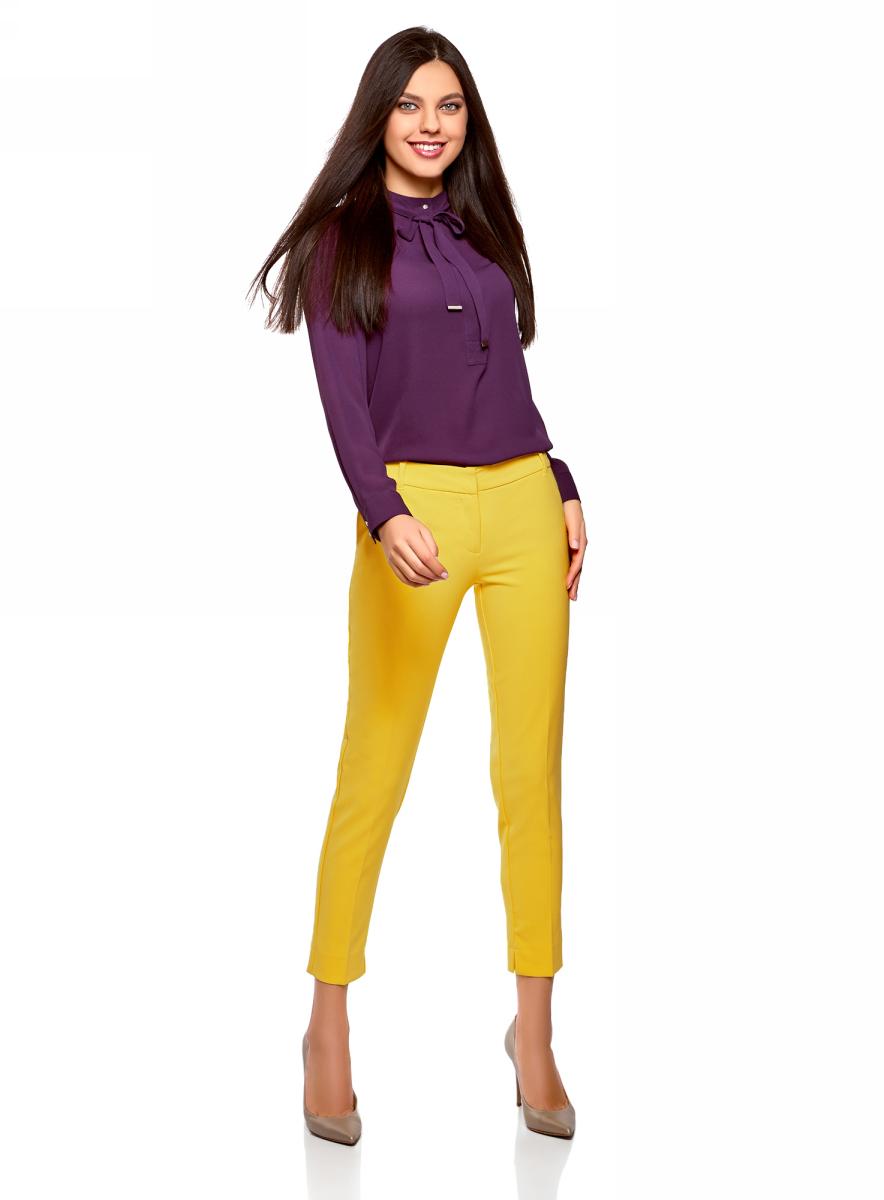 Брюки женские oodji Collection, цвет: желтый. 21701090B/42250/5100N. Размер 36 (42-170)21701090B/42250/5100NЖенские брюки oodji выполнены из качественной смесовой ткани. Брюки застегиваются на молнию и дополнены стрелками. Зауженная укороченная модель дополнена карманами и небольшими разрезами по низу брючин.