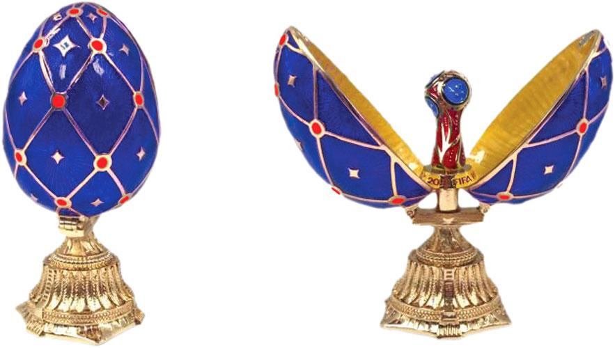 Яйцо пасхальное FIFA Кубок, цвет: синий, 4,5 х 4,5 х 9,1 смF-09-91-BLUEРоскошное произведение в великолепной стилистике известных яиц Фаберже, в котором кропотливо повторены лучшие находки знаменитого ювелира.Яйцо стоит на постаменте с богатой гравировкой, украшенной узорами. Раскрывается на две части, снаружи покрыто эмалью и орнаментальной сеткой, на пересечениях ячеек – сверкающие стразы. Внутри – искусная мини-копия кубка ЧМ, отделанная разноцветной эмалью.Это прекрасный подарок на память для каждого болельщика, достойный сувенир ЧМ-2018.