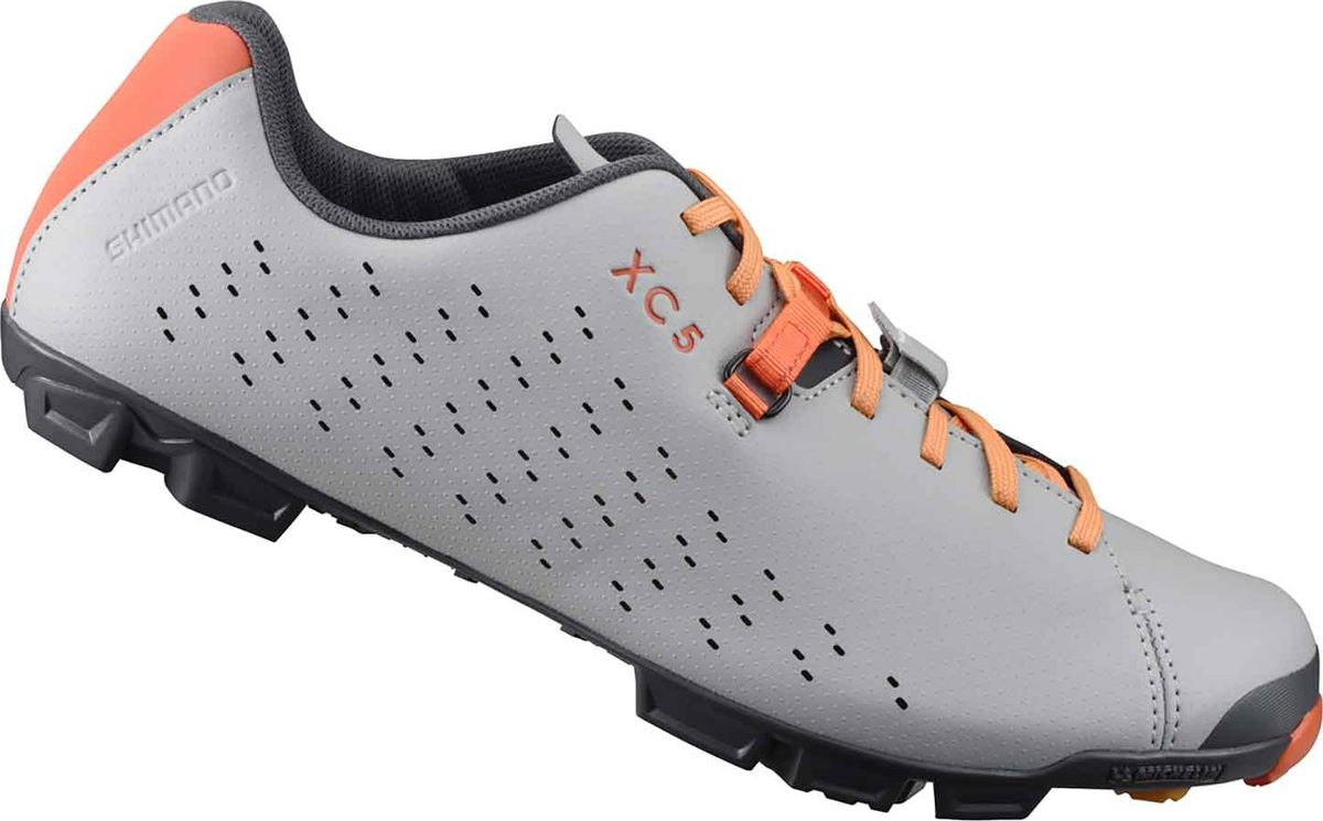 Велотуфли мужские Shimano SH-XC500, цвет: серый, оранжевый. Размер 43SH-XC500_серКомфортные и функциональные туфли для местности смешанного типаОсобенности Шнуровка с системой Mini Power Strap надежно удерживает стопу Легкая и жесткая прослойка подошвы, усиленная карбоновым волокном Мягкая синтетическая кожа с перфорацией для вентиляции и превосходным прилеганием Эксклюзивный грязеотталкивающий протектор Michelin, обеспечивающий превосходное сцепление Резиновый противоскользящий рисунок подошвы, повторяющий форму свода стопы Усиленное крепление шипов для экстремальных условий, в качестве опции возможно использование шипов 18 мм Включает дополнительные шнурки