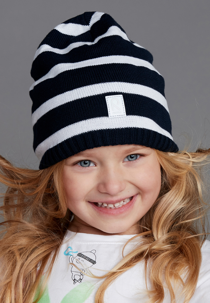 Шапка детская Reima Haapa, цвет: темно-синий, белый. 5285816981. Размер 565285816981Классическая хлопковая шапка просто незаменима в прохладную весеннюю пору! Эта детская шапка сшита из эластичного и дышащего хлопкового трикотажа на полуподкладке из гладкого хлопкового джерси.