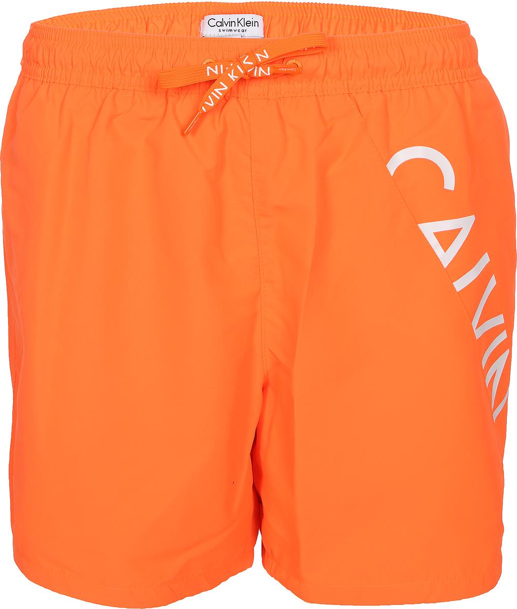 Шорты для плавания мужские Calvin Klein Underwear, цвет: оранжевый. KM0KM00168_807. Размер L (52)KM0KM00168_807Шорты для плавания от Calvin Klein выполнены из 100% полиэстера. Материал быстро сохнет. Модель с эластичной резинкой на талии и регулируемым шнурком.