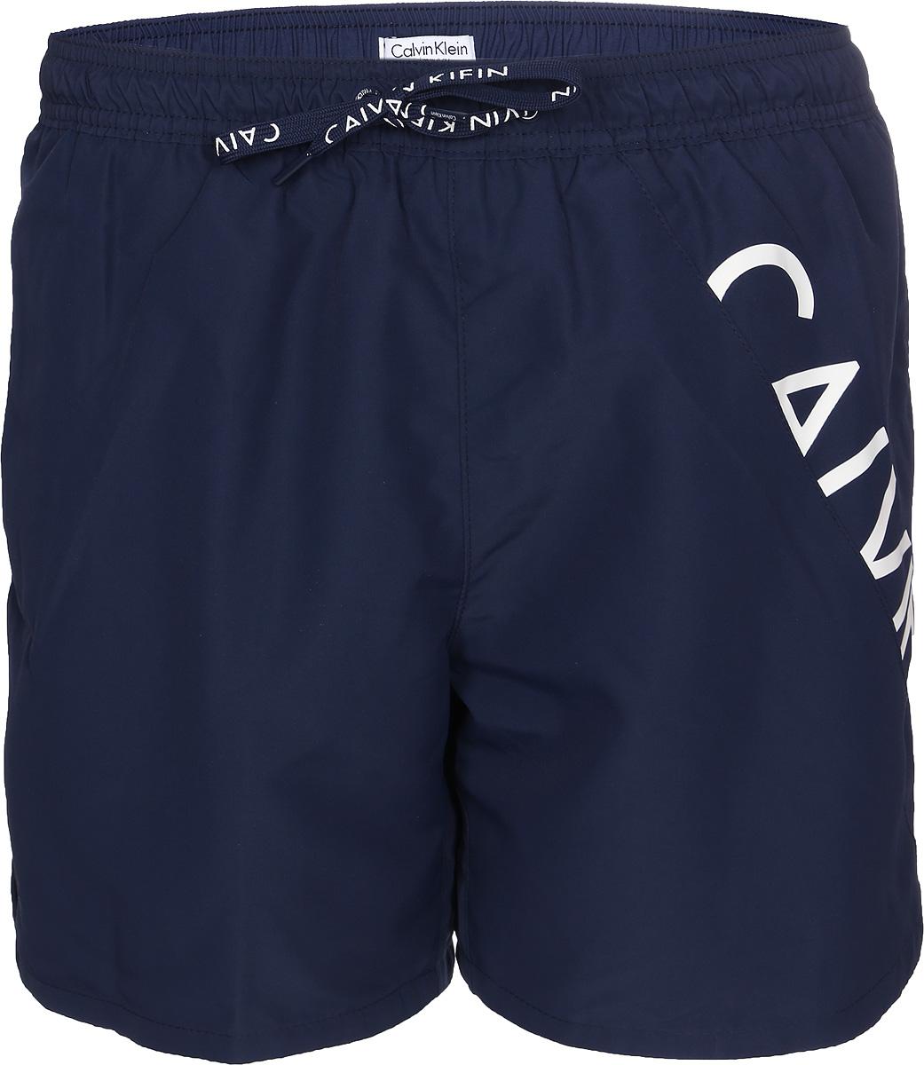 Шорты для плавания мужские Calvin Klein Underwear, цвет: темно-синий. KM0KM00168_470. Размер S (48)KM0KM00168_470Шорты для плавания от Calvin Klein выполнены из 100% полиэстера. Материал быстро сохнет. Модель с эластичной резинкой на талии и регулируемым шнурком.