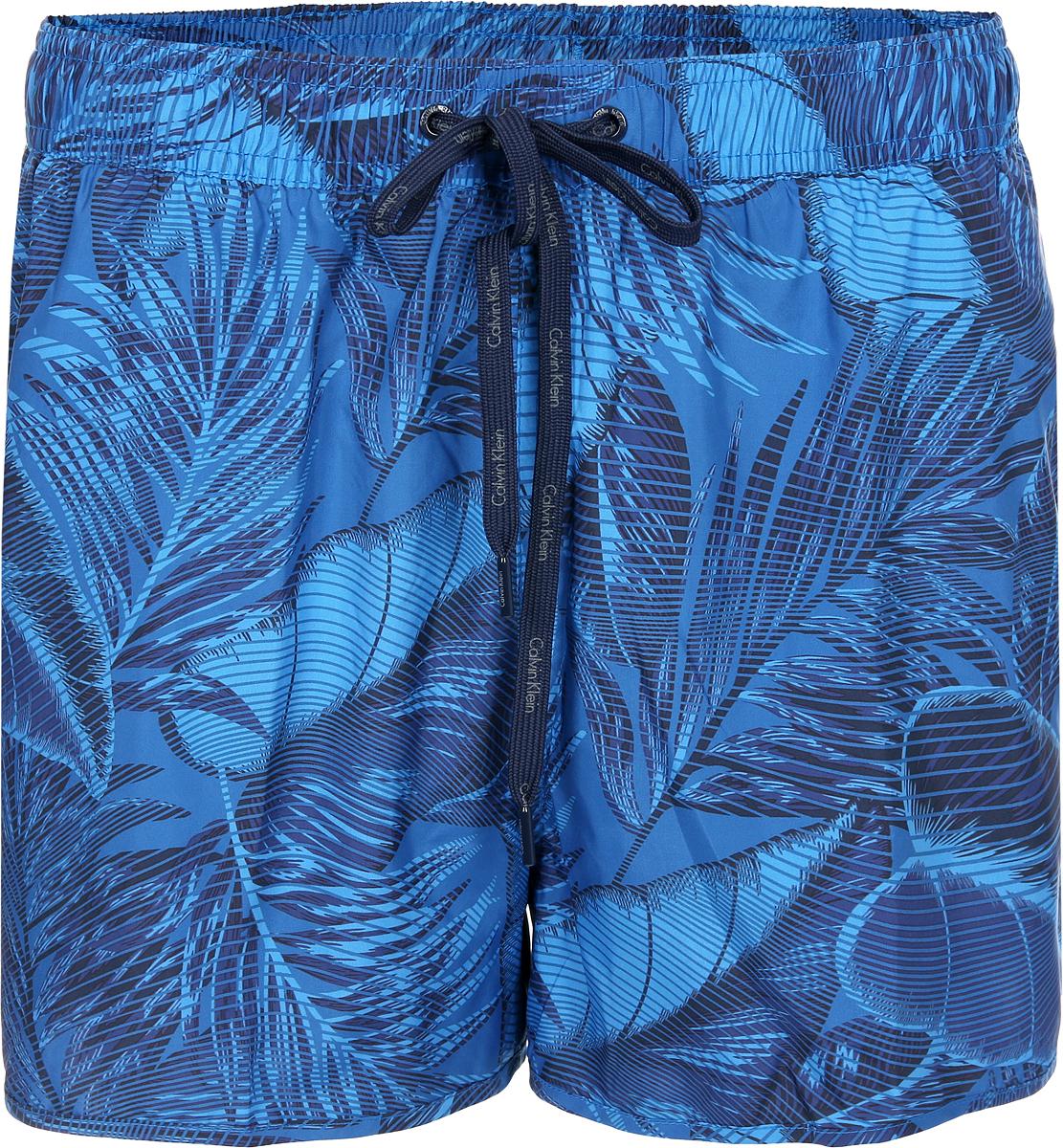 Шорты для плавания мужские Calvin Klein Underwear, цвет: синий. KM0KM00177_417. Размер M (50)KM0KM00177_417Мужские шорты для плавания Calvin Klein Underwear выполнены из полиэстера. Модель оформлена растительным принтом. Изделие имеет широкую эластичную резинку на поясе. Объем талии регулируется при помощи шнурка. Шорты дополнены одним накладным карманом сзади.