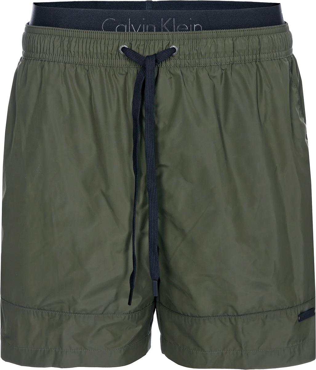 Шорты для плавания мужские Calvin Klein Underwear, цвет: темно-зеленый. KM0KM00213_314. Размер M (50)KM0KM00213_314Мужские шорты для плавания Calvin Klein Underwear выполнены из быстросохнущего материала. Модель имеет широкую эластичную резинку на поясе. Объем талии регулируется при помощи шнурка. Шорты дополнены накладным карманом сзади.