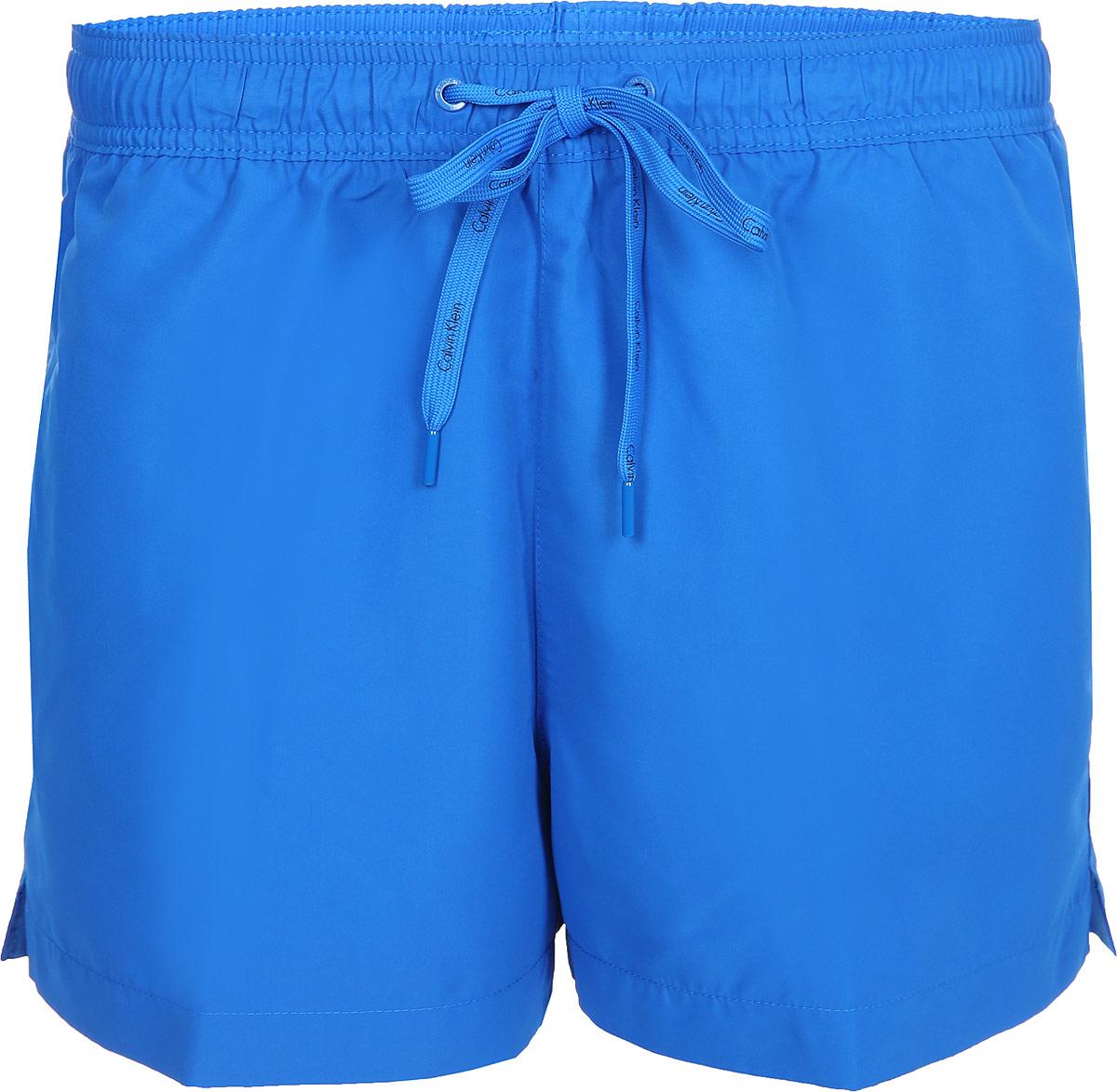 Шорты для плавания мужские Calvin Klein Underwear, цвет: синий. KM0KM00164_413. Размер XL (54)KM0KM00164_413Мужские шорты для плавания Calvin Klein Underwear выполнены из полиэстера. Изделие имеет широкую эластичную резинку на поясе. Объем талии регулируется при помощи шнурка. Шорты дополнены одним прорезным карманом сзади.