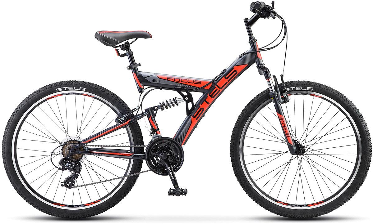 """Велосипед горный Stels Focus V 26 18-sp V030, цвет: черный, красный, диаметр колес 26, размер рамы 18LU086305Stels Focus V 26"""" 18-SP в версии 2018 года - двухподвес для поклонников комфортных поездок по неподготовленным трассам.Обновленный 18-скоростной Stels Focus обязательно понравится тем велопутешественникам, которые достаточно требовательны к своему байку, но при этом пока еще не обладают достаточным опытом катания в стиле кросс-кантри. Двухподвесы пользуются большой популярностью в нашей стране и неслучайно, так как способны обеспечить не только приличный уровень комфорта, но и подарить массу приятных впечатлений и новых открытий во время путешествий по мало затронутым цивилизацией местам.Сферы применения и преимущества велосипедов серии FocusДвухподвесы, в том числе, естественно, байки серии Focus, оптимальны для поездок в условиях бездорожья или по весьма некачественным асфальтированным трассам (коих у нас еще довольно много, в чем частично кроется секрет популярности моделей такого класса). Двухподвесам Focus по плечу и горные тропы, и лесопарковые зоны, и направления с большим количеством ям, кочек и выбоин, частые спуски и подъемы на трассе и другие сложные условия езды. В такой ситуации наличие нормально работающей передней и задней амортизации помогает гасить импульсы от точечных ударов и неровностей и позволяет избежать негативного влияния механического воздействия на ходовую часть велосипеда. Система амортизации Focus V 26 Sp 18 (2018)Если вы хотите без особых проблем кататься именно по таким трассам, то модель Stels Focus V 26"""" стала бы оптимальным решением. Она обладает сбалансированной комплектацией и приемлемой для своего класса ценой. При 18 скоростях и трансмиссии от Shimano он обеспечивает еще больше комфорта в поездке, то уже успели оценить многие владельцы моделей этой серии.Преимущества конструкции и оснащенияВ модели Stels Focus V26"""" все элементы максимально сбалансированы и гармонично сочетаются друг с другом. Как обычно, в первую очередь """