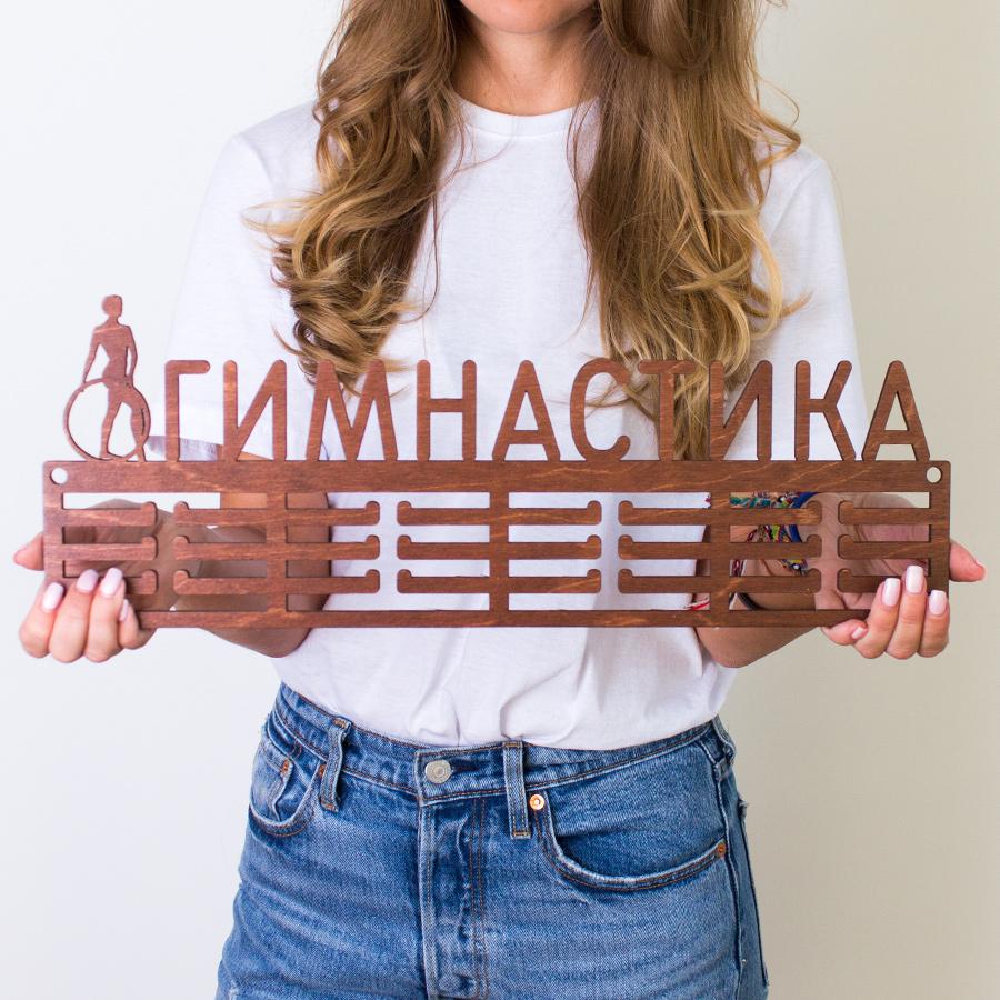 """Медальница Markov.Design """"Гимнастика"""" - практичный подарок для гимнастки. Медальница украсит интерьер и позволит красиво разместить медали на стене. Выполнена из фанеры, покрыта морилкой и лаком.Крепеж в комплекте.Цвет: коричневыйРазмер: 47 x 17 см"""