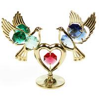 Фигурка декоративная Голуби с сердцем, цвет: золотистый10189Декоративная фигурка выполнена в виде двух голубей, которые держат сердце, и оформленных разноцветными кристаллами Сваровски. Фигурка будет вас радовать и достойно украсит интерьер вашего дома или офиса. Вы можете поставить украшение в любом месте, где оно будет удачно смотреться и радовать глаз. Кроме того, эта фигурка - отличный вариант подарка для ваших близких и друзей. Характеристики:Материал:металл, австрийские кристаллы. Размер: 9,5 см х 7 см х 3 см. Размер упаковки: 9 см х 10 см х 6 см. Производитель: Китай. Артикул: 67475.Более чем 30 лет назад компанияCrystocraftвыросла из ведущего производителя в перспективную торговую марку, которая задает тенденцию благодаря безупречному чувству красоты и стиля. Компания создает изящные, качественные, яркие сувениры, декорированные кристалламиSwarovskiразличных размеров и оттенков, сочетающие в себе превосходное мастерство обработки металлов и самое высокое качество кристаллов. Каждое изделие оформлено в индивидуальной подарочной упаковке, что придает ему завершенный и презентабельный вид.
