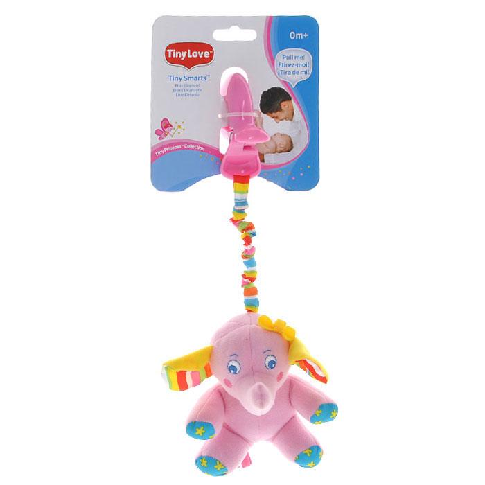 """Мягкая игрушка-подвеска """"Слоненок Елис"""" выполнена из текстильного материала различных цветов и фактур в виде улыбающегося розового слоника с маленьким бантиком на голове. Ушки слоненка содержат шуршащий элемент, а внутри туловища спрятана сфера, гремящая при тряске. К слоненку крепится текстильная веревочка. Если игрушку потянуть вниз, то она начнет вибрировать до тех пор, пока веревочка не вернется в исходное положение. С помощью пластиковой прищепки, игрушку легко можно прикрепить к кроватке, коляске или игровой дуге малыша. Игрушка подвеска """"Слоненок Елис"""" поможет ребенку в развитии цветового и звукового восприятия, мелкой моторики рук, координации движений и тактильных ощущений."""