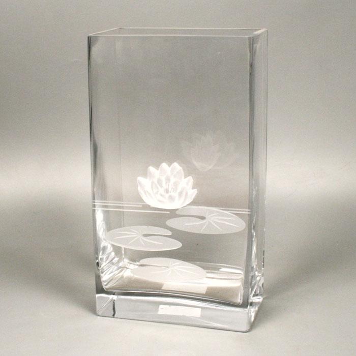 Вазон Deco-Glass, высота 27 смFS-80264Элегантный вазон Deco-Glass изготовлен из прозрачного стекла и декорирован объемной матовой лилией с рельефными листьями. Эксклюзивный вазон подчеркнет оригинальность интерьера и прекрасный вкус хозяина. Создайте в своем доме атмосферу уюта, преображая интерьер стильными, радующими глаза предметами. Также вазон может стать хорошим подарком вашим друзьям и близким. Характеристики:Материал:стекло. Размер вазона: 15 см х 8,5 см х 27 см. Размер упаковки: 16,5 см х 10 см х 29 см. Артикул: АС 04119/0270/АА-U0108.