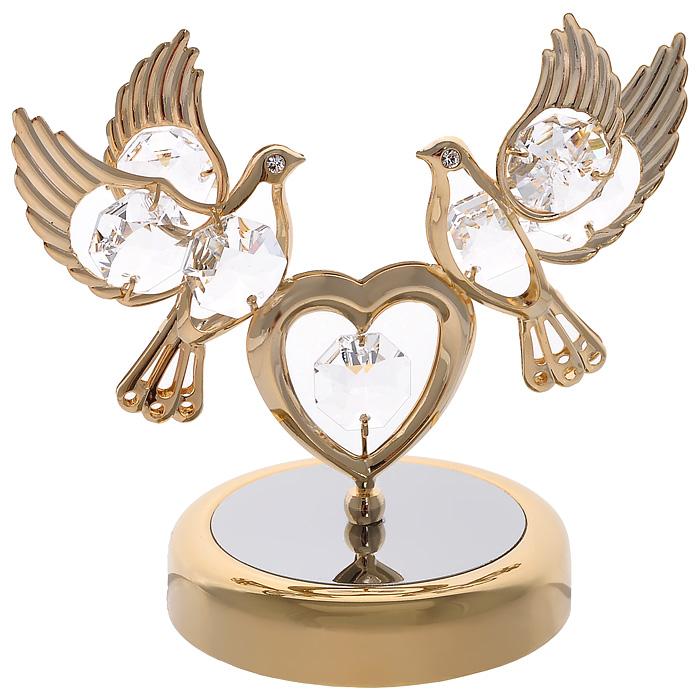 Фигурка декоративная Голуби с сердцем, цвет: золотистый90730Декоративная фигурка Голуби с сердцем, золотистого цвета, станет необычным аксессуаром для вашего интерьера и создаст незабываемую атмосферу. Фигурка выполнена в виде двух голубей, сидящих на сердце, и декорирована прозрачными кристаллами. Кристаллы, украшающие фигурку, носят громкое имяSwarovski. Ограненные, как бриллианты, кристаллы блистают сотнями тысяч различных оттенков.Эта очаровательная вещь послужит отличным подарком близкому человеку, родственнику или другу, а также подарит приятные мгновения и окунет вас в лучшие воспоминания.Фигурка упакована в подарочную коробку. Характеристики:Материал: металл (углеродистая сталь, покрытие золотом 0,05 микрон), австрийские кристаллы. Размер фигурки: 9 см х 8,5 см х 6 см. Цвет: золотистый. Размер упаковки: 9 см х 10 см х 6,5 см. Артикул: 67093. Более чем 30 лет назад компанияCrystocraftвыросла из ведущего производителя в перспективную торговую марку, которая задает тенденцию благодаря безупречному чувству красоты и стиля. Компания создает изящные, качественные, яркие сувениры, декорированные кристалламиSwarovskiразличных размеров и оттенков, сочетающие в себе превосходное мастерство обработки металлов и самое высокое качество кристаллов. Каждое изделие оформлено в индивидуальной подарочной упаковке, что придает ему завершенный и презентабельный вид.