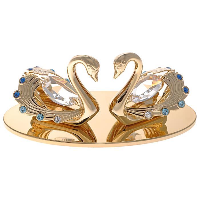 Фигурка декоративная Лебеди, цвет: золотистыйU210DFДекоративная фигурка Лебеди, золотистого цвета, станет необычным аксессуаром для вашего интерьера и создаст незабываемую атмосферу. Фигурка выполнена в виде пары лебедей, размещенных на подставке с зеркальной полировкой, и инкрустирована синими и голубыми кристаллами. Кристаллы, украшающие фигурку, носят громкое имяSwarovski. Ограненные, как бриллианты, кристаллы блистают сотнями тысяч различных оттенков.Эта очаровательная вещь послужит отличным подарком близкому человеку, родственнику или другу, а также подарит приятные мгновения и окунет вас в лучшие воспоминания.Фигурка упакована в подарочную коробку. Характеристики:Материал: металл (углеродистая сталь, покрытие золотом 0,05 микрон), австрийские кристаллы. Размер фигурки: 10 см х 5 см х 4,5 см. Цвет: золотистый. Размер упаковки: 7,5 см х 10 см х 5 см. Артикул: 67469. Более чем 30 лет назад компанияCrystocraftвыросла из ведущего производителя в перспективную торговую марку, которая задает тенденцию благодаря безупречному чувству красоты и стиля. Компания создает изящные, качественные, яркие сувениры, декорированные кристалламиSwarovskiразличных размеров и оттенков, сочетающие в себе превосходное мастерство обработки металлов и самое высокое качество кристаллов. Каждое изделие оформлено в индивидуальной подарочной упаковке, что придает ему завершенный и презентабельный вид.