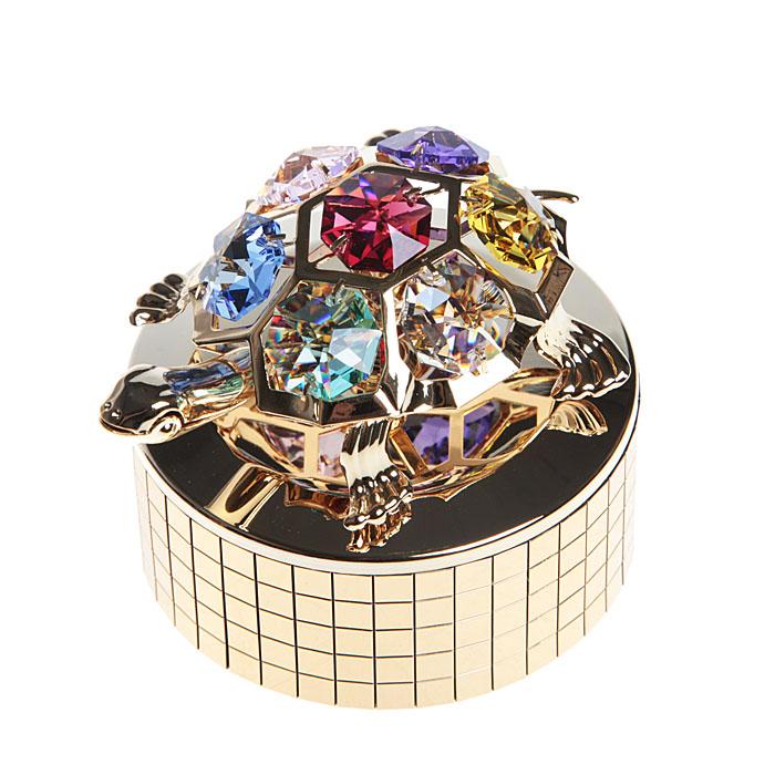 Фигурка декоративная Черепашка на музыкальной подставке25051 7_желтыйДекоративная фигурка Черепашка, золотистого цвета, станет необычным аксессуаром для вашего интерьера и создаст незабываемую атмосферу. Фигурка выполнена в виде черепашки, расположенной на крутящейся подставке с музыкальным механизмом, и инкрустирована крупными разноцветными кристаллами. Кристаллы, украшающие фигурку, носят громкое имя Swarovski. Ограненные, как бриллианты, кристаллы блистают сотнями тысяч различных оттенков. После завода фигурка крутится вместе с подставкой и играет легкая приятная мелодия. Эта очаровательная вещь послужит отличным подарком близкому человеку, родственнику или другу, а также подарит приятные мгновения и окунет вас в лучшие воспоминания. Фигурка упакована в подарочную коробку. Характеристики: Диамент основания: 6,5 см. Высота: 6 см. Материал: металл (углеродистая сталь, покрытие золотом 0,05 микрон), австрийские кристаллы.Более чем 30 лет назад компания Crystocraft выросла из ведущего производителя в перспективную торговую марку, которая задает тенденцию благодаря безупречному чувству красоты и стиля. Компания создает изящные, качественные, яркие сувениры, декорированные кристаллами Swarovski различных размеров и оттенков, сочетающие в себе превосходное мастерство обработки металлов и самое высокое качество кристаллов. Каждое изделие оформлено в индивидуальной подарочной упаковке, что придает ему завершенный и презентабельный вид.