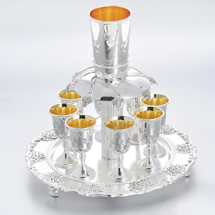 Набор коньячный Marquis Роза с дозатором, 9 предметов. 1076-MRVT-1520(SR)Коньячный набор Marquis Роза состоит из 8 рюмок на тонких ножках и подставки с дозатором. Предметы набора, выполненные из стали с серебряно-никелевым покрытием, оформлены изящной гравировкой в виде розы. Внутренняя поверхность рюмок и дозатора - золотистого цвета. Рюмки устанавливаются на подставку, коньяк наливается в кружку-дозатор и из нее выливается в основание, из которого по желобкам коньяк разливается на ровные части по стопкам. Выполненный под старину, такой набор придется по вкусу и ценителям классики, и тем, кто предпочитает утонченность и изысканность. Коньячный набор Marquis оригинального дизайна и безукоризненного качества станет украшением вашего стола. Характеристики:Материал: сталь, пластик. Цвет: серебристый, золотистый. Диаметр рюмки по верхнему краю: 4 см. Высота рюмки: 8,5 см. Диаметр дозатора по верхнему краю: 6 см. Высота дозатора: 8,5 см. Диаметр подставки: 26 см. Высота подставки (без учета дозатора): 19 см. Размер упаковки: 26 см х 26 см х 20 см. Артикул: 1076-MR.