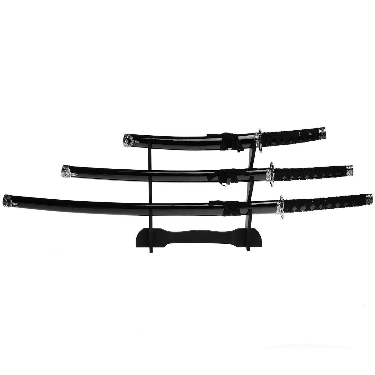 Набор самурайских мечей на подставке, 3 шт. 45426341619Самурайский меч соединяет в себе духовный и материальный миры, физическое и духовное начало... Набор самурайских мечей состоит из длинного меча - катаны, среднего - вакидзаси и короткого меча - танто. Изготовлены они в традиционном японском стиле из стали, ножны украшены плетением из текстильного шнурка. Этот набор - изысканный подарок поклонникам культуры Востока и прекрасное дополнение интерьера вашей квартиры или офиса. В качестве настенного украшения самурайские мечи использовались еще с древности, знаменуя собой подвиги славных предков. Благодаря специальной подставке, вы можете не только повесить мечи на стену, но и поставить в любое удобное для вас место. Характеристики:Материал:металл, пластик, дерево, текстиль.Длина мечей: 100 см; 81 см; 54 см.