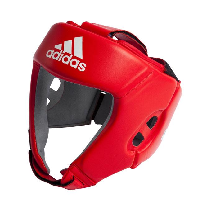 Шлем боксерский Adidas AIBA, цвет: красный. AIBAH1. Размер XL (56-60 см)AIBAH1Боксерский шлем Adidas AIBA разработан и спроектирован для обеспечения максимальной защиты и оптимальной видимости. Шлем сертифицирован Международной ассоциацией бокса (AIBA). Оболочка шлема изготовлена из натуральной кожи, что увеличивает срок эксплуатации шлема. Внутреннее наполнение из пены, изготовленной по технологии Air Cushion, обеспечивает отличную амортизацию ударных нагрузок. Внутренняя подкладка выполнена из высокотехнологичной, искусственной кожи Amara. Шлем имеет легкую конструкцию без защиты скул. Два широких ремня фиксируемых липучкой на теменной части и два ремня на липучке в затылочной части позволяют регулировать размер шлема и обеспечивают плотную и удобную посадку, исключая смещение шлема во время боя. Так же шлем имеет регулируемый ремешок под подбородком.
