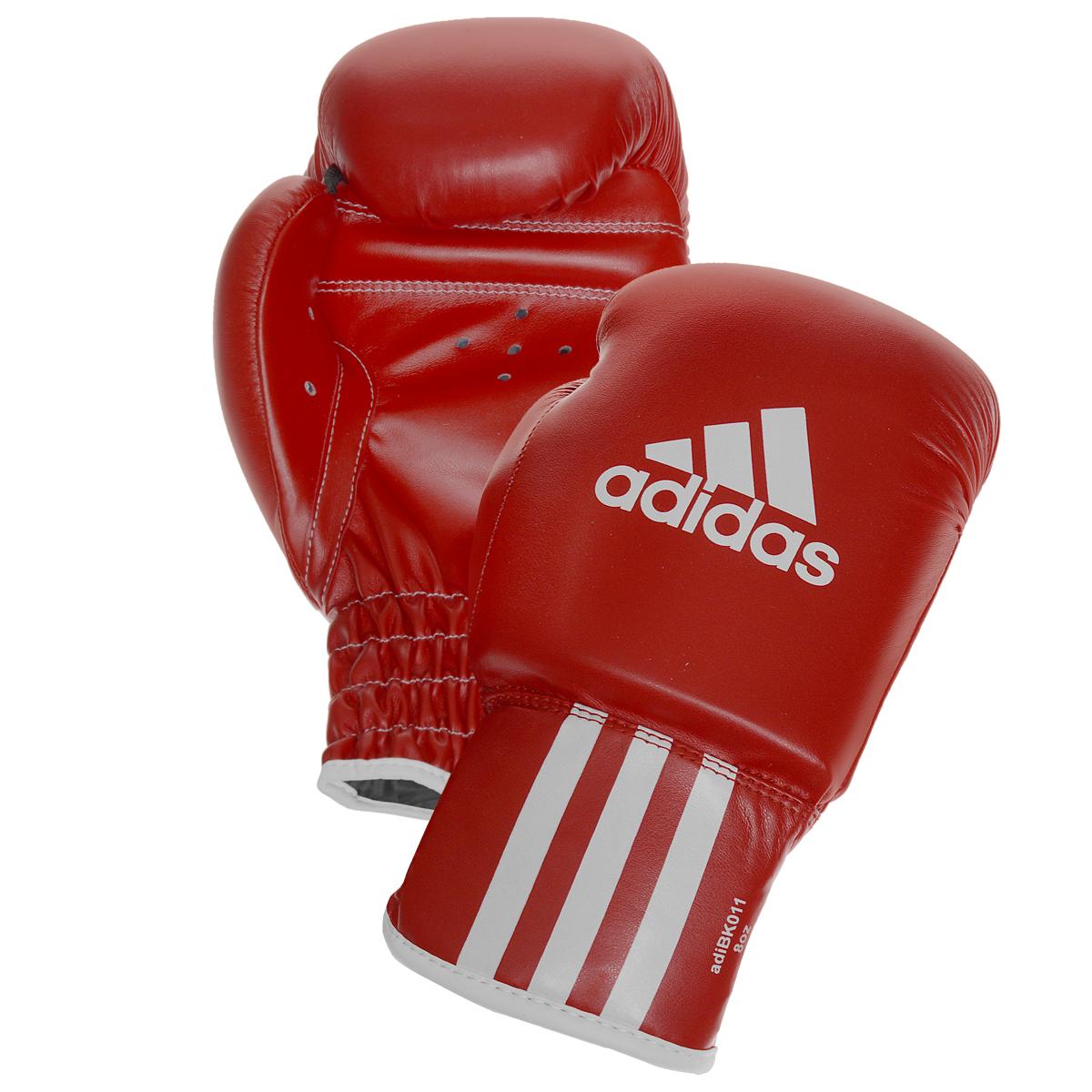 Перчатки боксерские Adidas Rookie-2, цвет: красный. adiBK011. Вес 8 унцийBB1637Боксерские перчатки Adidas Rookie-2 изготовлены из мягкого полиуретана, который по своим качествам не уступает натуральной коже. Внутренний наполнитель из многослойной пены обеспечивет надежную защиту рук боксера и позволяя безопасно тренироваться в полную силу. Предварительно изогнутый крой перчатки позволяет боксеру держать кулак в правильном положении. Загнутый параллельно кулаку большой палец обеспечивает безопасность при нанесении ударов и защищает большой палец от вывихов и травм. Внутренняя подкладка и вентиляционные отверстия на ладони создают максимальный уровень комфорта для рук, поддерживая оптимальный микроклимат внутри перчаток.