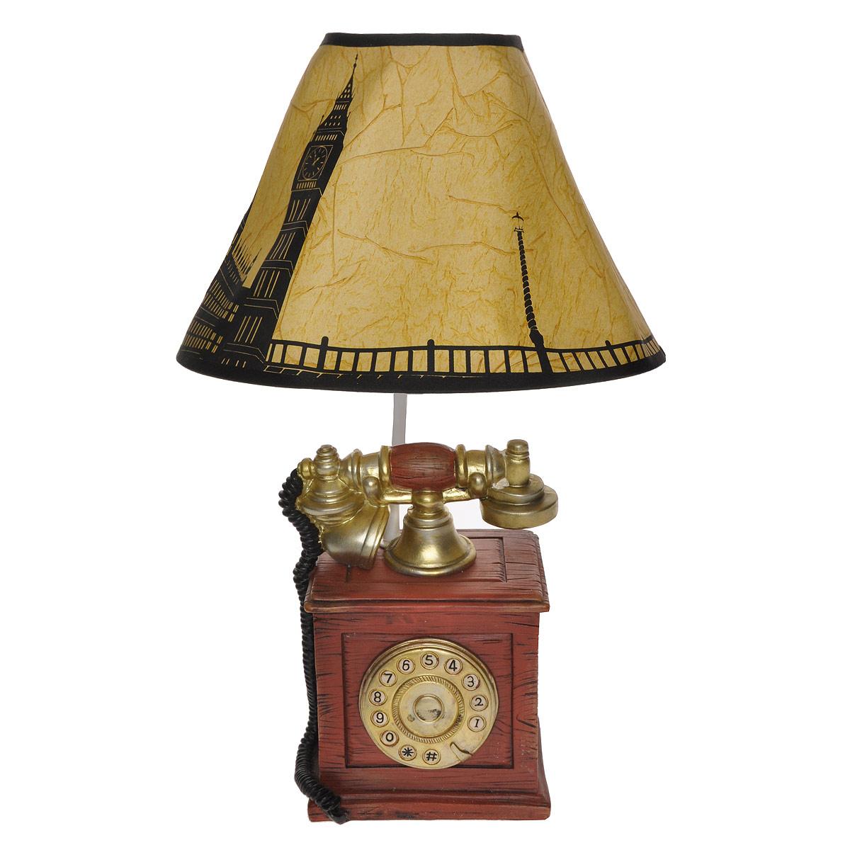 Светильник настольный Телефон. 29349LSL-8001-01Настольный светильник Телефон, изготовленный из полирезины, выполнен в виде старинного телефона и оформлен картонным абажуром с графическим рисунком города. Такой светильник прекрасно подойдет для украшения интерьера и создания атмосферы тепла и уюта. Внутри светильника расположена лампа накаливания. Светильник работает от электросети и включается при помощи кнопки на шнуре.Характеристики: Материал: полистоун, металл, пластик, картон. Высота светильника: 40 см. Диаметр абажура: 26 см. Размер основания светильника: 14 см х 11 см. Мощность лампы: 40 Вт (входит в комплект). Цоколь: Е27. Напряжение: 220 В, частота 50 Гц.