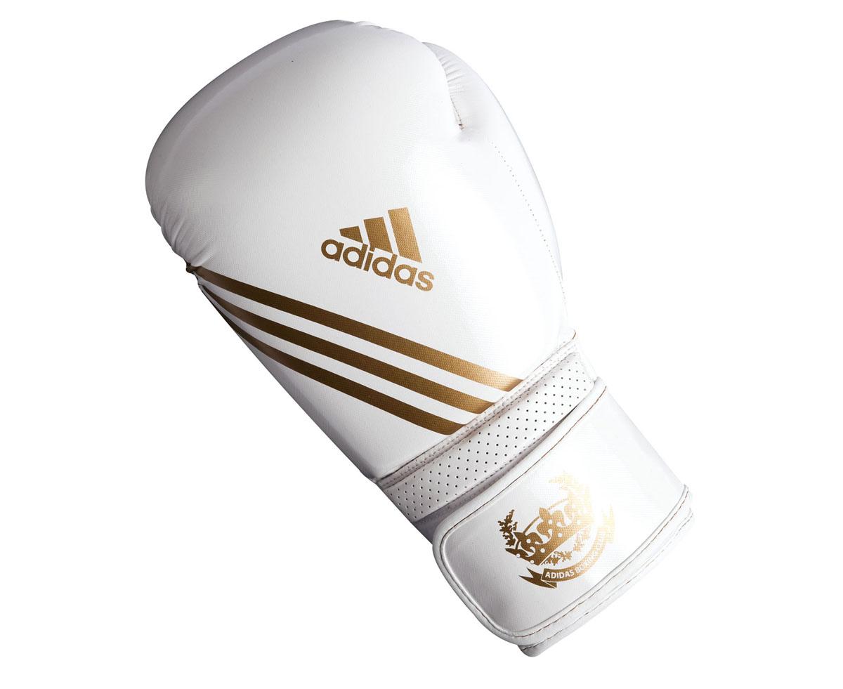 Перчатки боксерские Adidas Hybrid Aero Tech, цвет: бело-золотой. adiBL06. Вес 8 унций661.22Боксерские перчатки Adidas Hybrid Aero Tech изготовлены из полиуретана PU4G, который по своим качествам не уступает натуральной коже. Внутренний наполнитель из многослойной пены закрывает тыльную сторону и боковую часть ладони, обеспечивая надежную защиту рук боксера и позволяя безопасно тренироваться в полную силу. Загнутый параллельно кулаку большой палец обеспечивает безопасность при нанесении ударов и защищает большой палец от вывихов и травм. Вентиляционные отверстия на ладони создают максимальный уровень комфорта для рук, поддерживая оптимальный микроклимат внутри перчаток. Широкий ремень, охватывая запястье, полностью оборачивается вокруг манжеты, благодаря чему создается дополнительная защита лучезапястного сустава от травмирования. Застежка на липучке способствует быстрому и удобному одеванию перчаток, плотно фиксирует перчатки на руке.