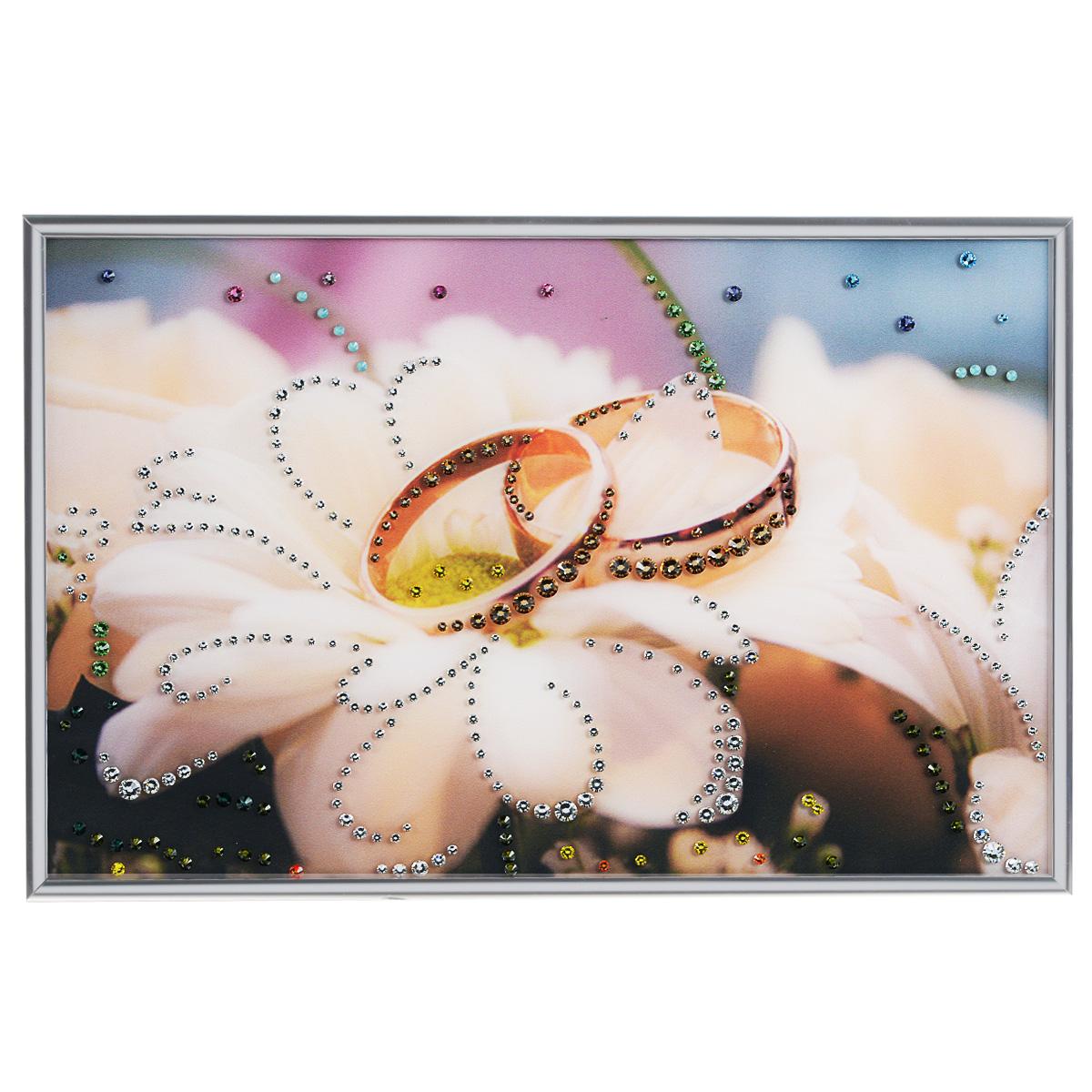 Картина с кристаллами Swarovski Обручальное кольцо, 30 х 20 см1082Изящная картина в металлической раме, инкрустирована кристаллами Swarovski, которые отличаются четкой и ровной огранкой, ярким блеском и чистотой цвета. Красочное изображение обручальных колец, расположенное под стеклом, прекрасно дополняет блеск кристаллов. С обратной стороны имеется металлическая петелька для размещения картины на стене.Картина с кристаллами Swarovski Обручальное кольцо элегантно украсит интерьер дома или офиса, а также станет прекрасным подарком, который обязательно понравится получателю. Блеск кристаллов в интерьере, что может быть сказочнее и удивительнее. Картина упакована в подарочную картонную коробку синего цвета и комплектуется сертификатом соответствия Swarovski.
