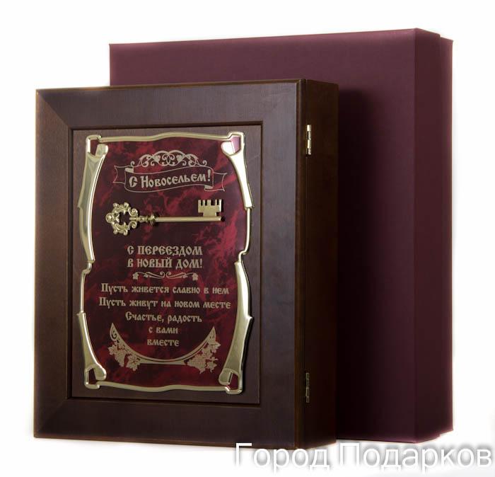 Ключница Ключ С Новосельем! С переездом в новый дом…, 36,5 х 32 см, подарочная коробка36241Настенная ключница из натурального дерева, с натурального деревас внутренней бархатной отделкой, декорированна метализированной пластиной с лазерной гравировкой и накладкой, упакованна в подарочный футляр, размер 36,5х32х7 см, коричневый/золотой