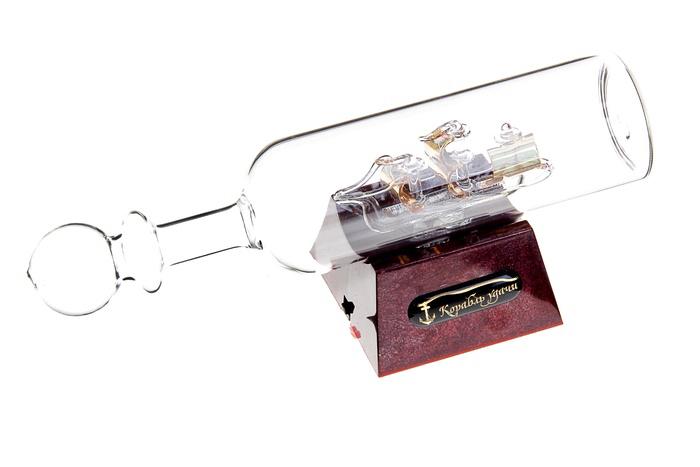 Корабль сувенирный в бутылке Корабль удачи, с подсветкой, длина 20 см. 295006a030073Сувенирный корабль в бутылке Корабль удачи - прекрасный сувенир и великолепный элемент декора рабочей зоны в офисе или кабинете. В прозрачную бутылку помещена фигурка трехмачтового корабля с золотыми парусами. Для бутылки предусмотрена пластиковая подставка, украшенная надписью Корабль удачи. Стремящиеся в неизведанную даль, словно невесомые паруса заиграют по-новому, если вы включите яркую подсветку. Время идет, и мы становимся свидетелями развития технического прогресса, новых учений и практик. Но одно не подвластно времени - это любовь человека к морю и кораблям. Сувенирный корабль в бутылке наполнен историей и силой океанских вод. Данная модель кораблика станет отличным подарком для всех любителей морей, поклонников историй о покорении океанов и неизведанных земель. Модель корабля - подарок со смыслом. Издавна на Руси считалось, что корабли приносят удачу и везение. Поэтому их изображение и точные копии всегда присутствовали в помещениях. Удивите себя и своих близких необычным презентом. Подсветка работает от 3 батареек типа ААА (в комплект не входят). Длина бутылки: 20 см. Диаметр бутылки: 4,5 см. Размер подставки: 6,5 см х 6,5 см х 3,5 см.