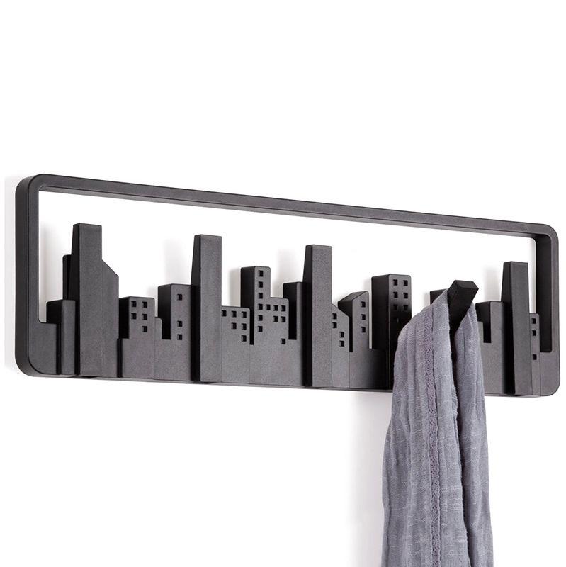 Вешалка настенная Umbra Skyline, цвет: черный, 5 крючковCLP446Силуэт оригинальной вешалки Umbra Skyline всем знаком: открывающийся из окна вид на мегаполис. В череде разновысотных домов-параллелепипедов можно увидеть пять самых высоких небоскребов - они представляют собой замаскированные крючки для одежды. При необходимости крючки откидываются и используются по назначению. Каждый крючок выполнен из прочного пластика и выдерживает нагрузку до 2,3 кг. Вешалка Umbra Skyline идеально подходит для маленьких прихожих и ограниченных пространств. Размер вешалки: 50 см х 14 см х 1,5 см.