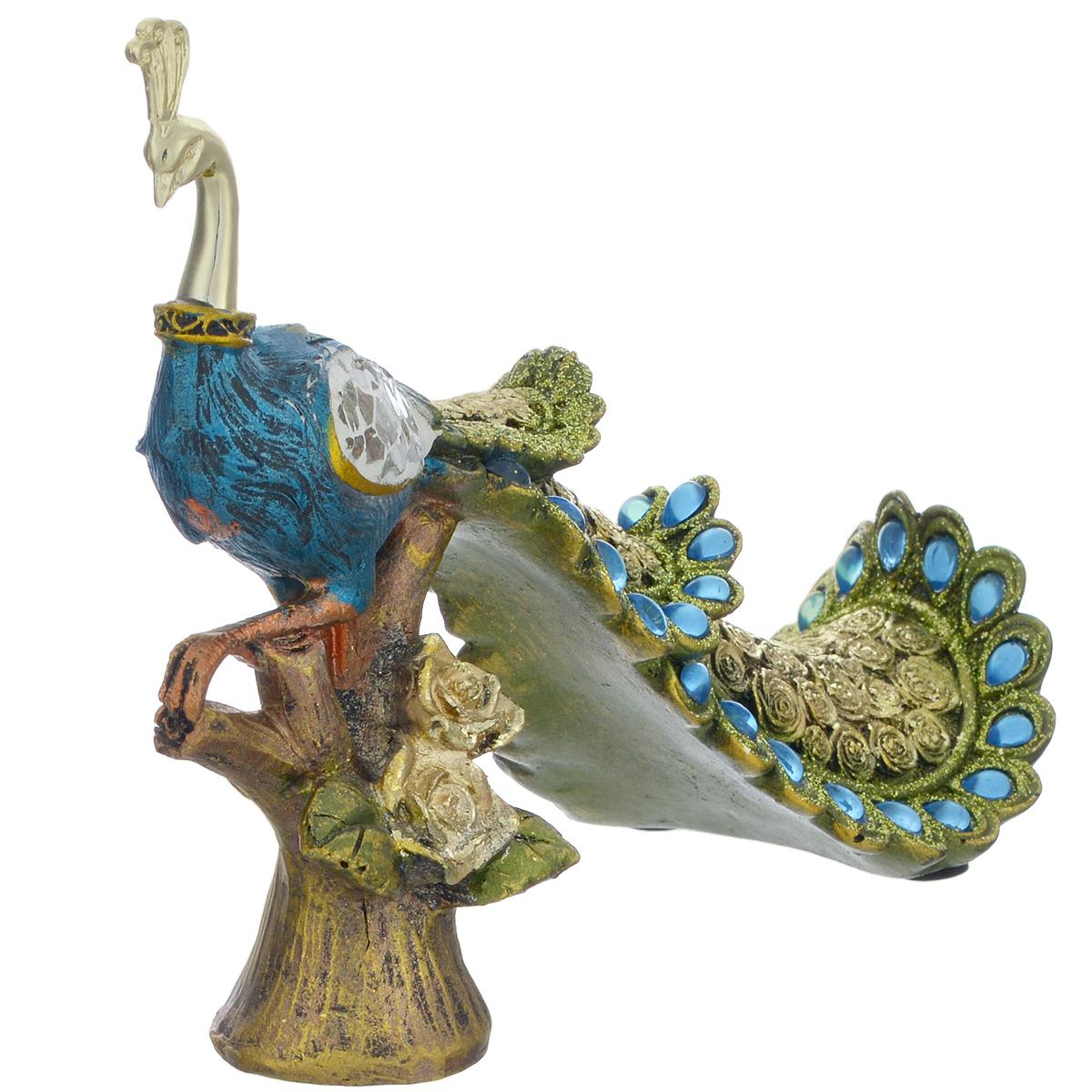 Фигурка декоративная Molento Райская птица, высота 14 смTHN132NДекоративная фигура Molento Райская птица, изготовленная из полистоуна, позволит вам украсить интерьер дома, рабочего кабинета или любого другого помещения оригинальным образом. Изделие, выполненное в виде павлина, оформлено рельефным рисунком, блестками, стразами и зеркальной россыпью.С такой декоративной фигурой вы сможете не просто внести в интерьер элемент оригинальности, но и создать атмосферу загадочности и изысканности.Размер фигурки: 19 см х 7 см х 20,5 см.