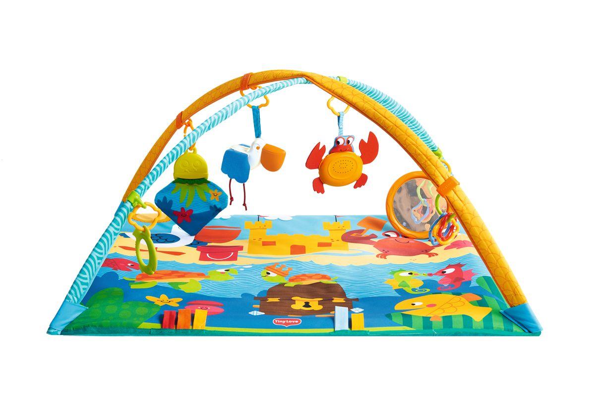 """Развивающий коврик Tiny Love """"Морские приключения"""" поможет развлечь и занять малыша в течение нескольких часов. Коврик легко раскладывается. Сверху крепятся большие дуги, на которые можно разместить подвесные игрушки и другие аксессуары. В 1-3 месяца малышу необходимо повесить игрушки в зону видимости, чтоб была возможность разглядывать и изучать разнообразные фигурки и цвета. С 3-6 месяцев ребенок начинает самостоятельно переворачиваться со спинки на бочок, с живота на спинку. Лежа на животике ребенок может увлечься игрой с медузой и зеркалом. С 6-9 месяцев наиболее интересным для ребенка станет музыкальный краб, который издает забавные звуки и позволяет ребенку изучать причинно-следственные связи. Яркие рисунки стимулируют зрение, а наличие объемных фигурок поможет в развитии мелкой моторики рук. Коврик можно стирать в стиральной машинке. Рекомендуется докупить 3 батарейки типа АG13 (товар комплектуется демонстрационными)."""