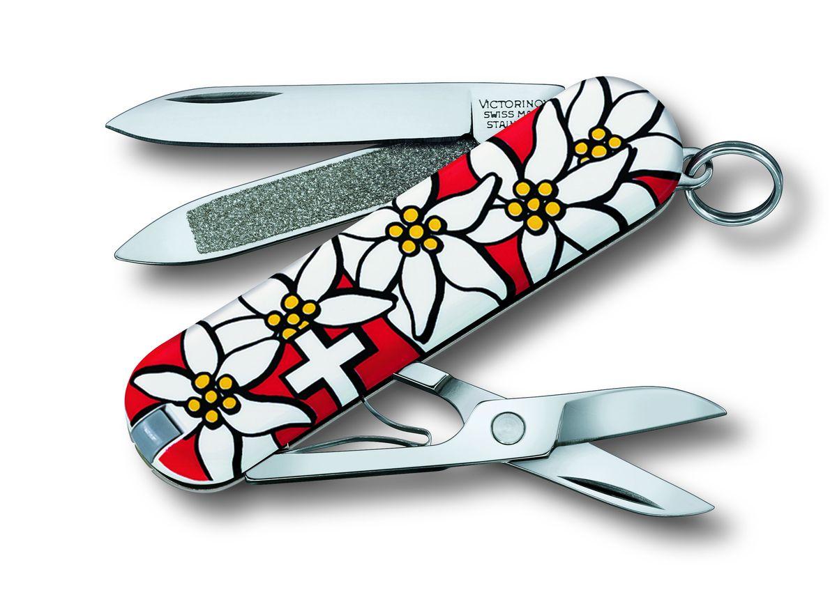Нож-брелок Victorinox Classic Edelweiss 0.6203.840, цвет: красный, белый0.6203.840Перочинный нож CLASSIC имеет 7 функций: 1. Лезвие2. Пилка для ногтей с: 3. – Инструментом по уходу за ногтями4. Ножницы5. Кольцо для ключей6. Пинцет7. ЗубочисткаДизайн рукояти: EdelweissВ комплекте: чёрный чехол из искусственной кожи