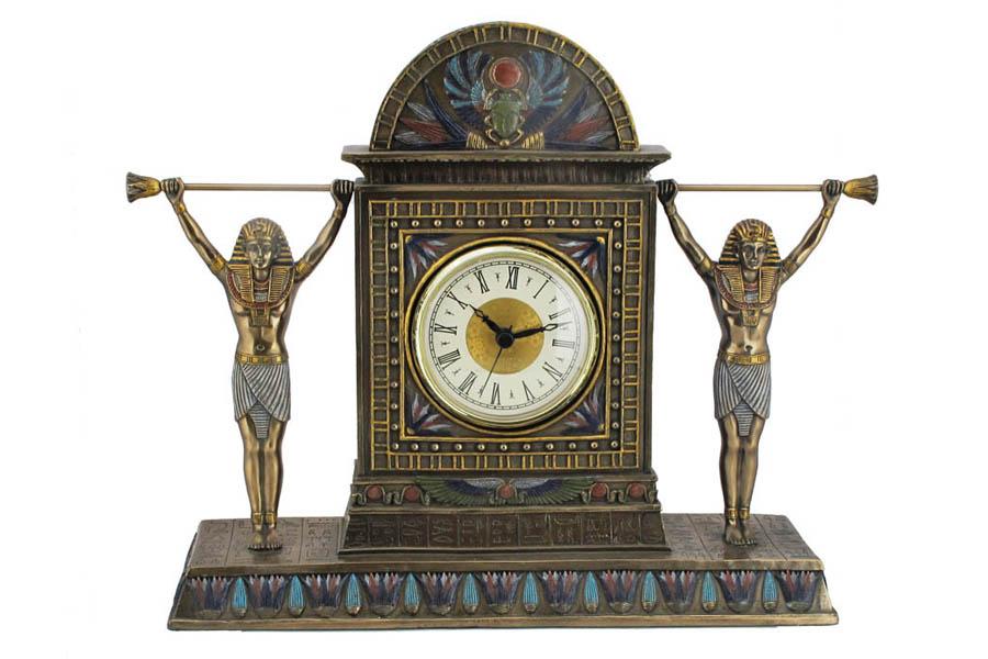 Часы каминные Veronese Египет, 34 х 9,5 х 26,5 смVWU73561V4ALЧасы каминные Veronese Египет изготовлены из полистоуна бронзового цвета. Изделие декорировано изысканным рельефом и дополнено двумя фигурками в виде египетских фараонов. Часы имеют круглый циферблат с индикацией римскими цифрами. Роскошные часы прекрасно дополнят интерьер дома и займут свое достойное место на каминной полке.